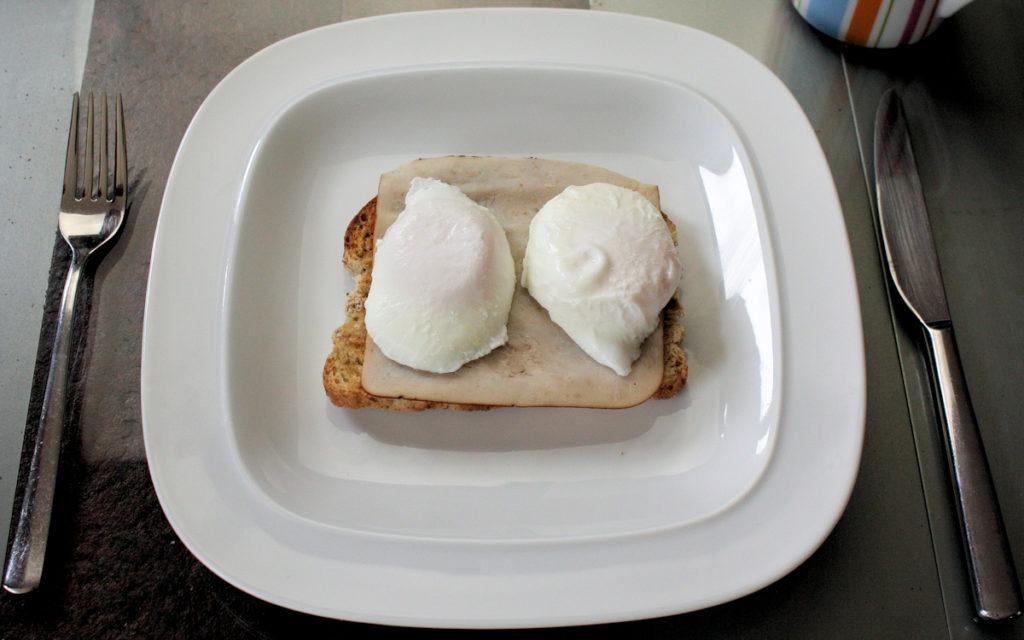 Poached eggs on roast turkey on multigrain toast for breakfast or lunch